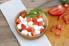 Sliced tomatoes, basil and mozzarella cheese on a wooden plate. Selective focus Royalty Free Stock Photos