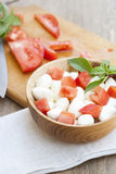Sliced tomatoes, basil and mozzarella cheese on a wooden plate. Selective focus Stock Image