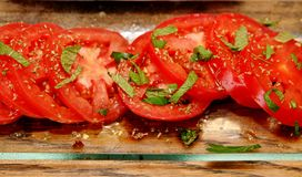 Sliced tomatoes with basil. Sliced red tomatoes with shredded basil on a glass plate Stock Image