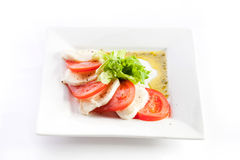 Sliced tomatoes and cheese with lettuce on a white background Stock Image