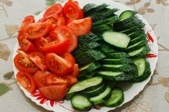 Sliced tomatoes and cucumbers lie on a plate, royalty free stock photography