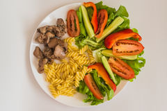 Sliced tomatoes, cucumbers, pasta, liver. Sliced tomatoes, cucumbers, lettuce, boiled pasta and fried chicken liver in the white plate on a white background Royalty Free Stock Photo