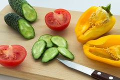 Sliced tomatoes, cucumbers, peppers and knife on the table Royalty Free Stock Photos