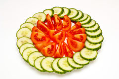 Sliced tomatoes and cucumbers on plate isolated Royalty Free Stock Image