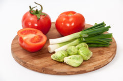 Sliced tomatoes, onions and brussels sprouts on the wooden board Stock Photography