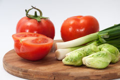 Sliced tomatoes, onions and brussels sprouts on the wooden board Stock Images