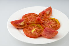 Sliced tomatoes. White porcelain plate, put tomato slices, the taste is sweet Royalty Free Stock Images