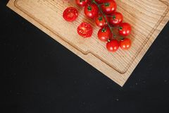 Sliced tomatoes on a wooden cutting Board. On black chalkboard. Black background with copy space royalty free stock photos