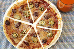 Sliced Tortilla Pizza. Tortilla crust thin pizza topped with tomato paste, mozzarella cheese, jalapenos, kalamata olives and pepper near a clear glass cup of Royalty Free Stock Photo