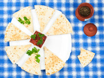 Sliced tortillas with basil on platter. And blue napkin Royalty Free Stock Photo