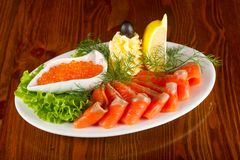 Sliced trout and red caviar. Served lemon royalty free stock photo