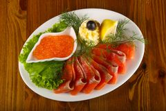 Sliced trout and red caviar. Served lemon royalty free stock images