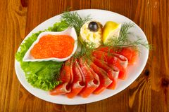 Sliced trout and red caviar. Served lemon Stock Photography