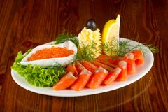 Sliced trout and red caviar. Served lemon stock photos