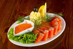 Sliced trout and red caviar. Served lemon stock image