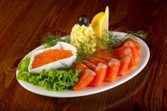 Sliced trout and red caviar. Served lemon royalty free stock photos