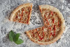 Sliced tuna pizza and green leaves on dark background with scattered white flour. Directly above photo. Directly above photo stock photo