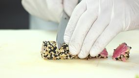 Sliced tuna with sesame seeds. Hands cutting fish close up stock video footage