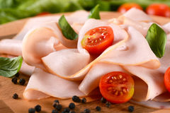 Sliced turkey breast. Appetizer of sliced turkey breast rolled up on the cutting board royalty free stock photography
