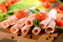 Sliced turkey breast. Appetizer of sliced turkey breast rolled up on the cutting board royalty free stock images