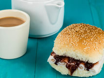 Sliced Turkey and Cranberry Sauce Bread Roll With a Cup of Tea. Sliced Turkey and Cranberry Sauce Bread Roll Against a Blue Background royalty free stock image
