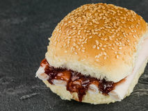 Sliced Turkey and Cranberry Sauce Bread Roll In A Sesame Bun. Sliced Turkey and Cranberry Sauce Bread Roll Against a Black Slate Tile Background royalty free stock image