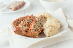 Sliced turkey meatloaf. A plate of sliced turkey meatloaf with spinach and sundried tomatoes with a side of mashed red potates stock photo