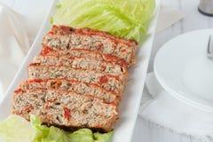 Sliced turkey meatloaf. A serving platter of sliced turkey meatloaf with spinach and sundried tomatoes stock image