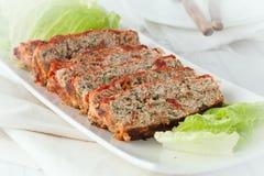 Sliced turkey meatloaf. A serving platter of sliced turkey meatloaf with spinach and sundried tomatoes royalty free stock images