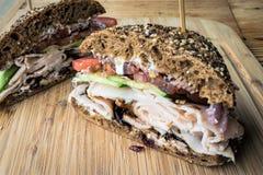 Sliced Turkey sandwich on wooden platter. Sliced turkey sandwich stacked with ingredients on wooden platter with wooden table background stock photography