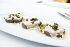 Sliced veal with sauce. Sliced veal covered with a creamy tuna-caper sauce stock photos