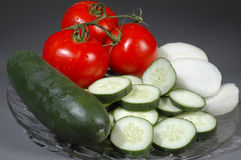 Sliced vegetables. Horizontal shot of sliced onions, sliced cucumbers, tomato Stock Photos