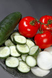 Sliced vegetables. Vertical shot of sliced onions, sliced cucumbers, tomato Royalty Free Stock Image