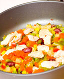 Sliced vegetables and chicken in pan Royalty Free Stock Images
