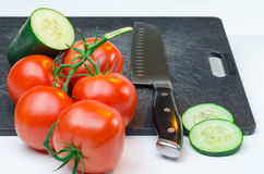Sliced vegetables on Cutting Board. Green and red vegetables sliced on black cutting board Stock Images