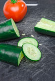 Sliced vegetables on Cutting Board. Green and red vegetables sliced on black cutting board Stock Photo