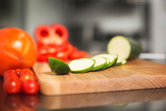 Sliced vegetables on cutting board. Portrait of sliced cucumber and pepper on cutting board and tomatoes next to Stock Photos