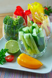 Sliced vegetables. Fresh sliced cucumber, red and yellow pepper, apple and broccoli in a glass Stock Images