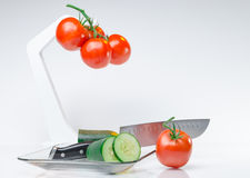 Sliced vegetables on Glass Plate and hook white background. Red  tomatoes on hook and cucumber vegetables sliced on white backdrop in glass plate Royalty Free Stock Image