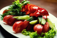 Sliced vegetables on a plate.Platter of assorted fresh vegetable. S.Healthy vegetarian Salad with Tomatoes, cucumbers, peppers and greens.Healthy eating habits Royalty Free Stock Image