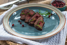 Sliced venison steak. On a plate with lingonberries royalty free stock image