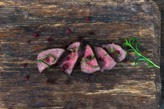 Sliced venison steak. On wooden board with lingonberries - top view stock photos