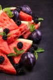 Sliced watermelon with blackberries and mint leaves on black backgroung. Healthy vegetarian food. Watermelon slices and mint leaves on white backgroung. А stock photos