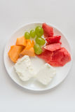Sliced watermelon, cantaloupe, cheese, grapes. Sliced watermelon, cantaloupe, cottage cheese and green grapes in a white plate on a white background royalty free stock photography