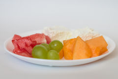 Sliced watermelon, cantaloupe, cheese, grapes. Sliced watermelon, cantaloupe, cottage cheese and green grapes in a white plate on a white background stock photos