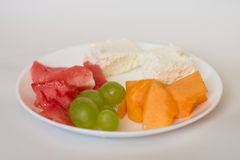 Sliced watermelon, cantaloupe, cheese, grapes. Sliced watermelon, cantaloupe, cottage cheese and green grapes in a white plate on a white background royalty free stock images