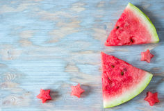 Sliced watermelon with carved stars on wooden background Royalty Free Stock Photography