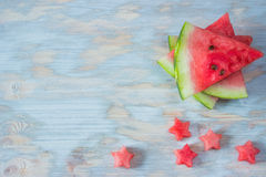 Sliced watermelon with carved stars on wooden background Royalty Free Stock Image