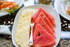Sliced Watermelon and Pineapple Fruit With Stainless Steel Fork Placed on White Ceramic Rectangular Plate Stock Images