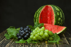 Sliced watermelon, red and green grapes on a wooden table Stock Photo